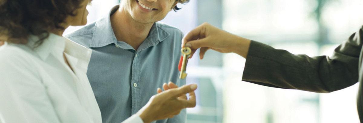 Hand übergibt Schlüssel an andere Hand